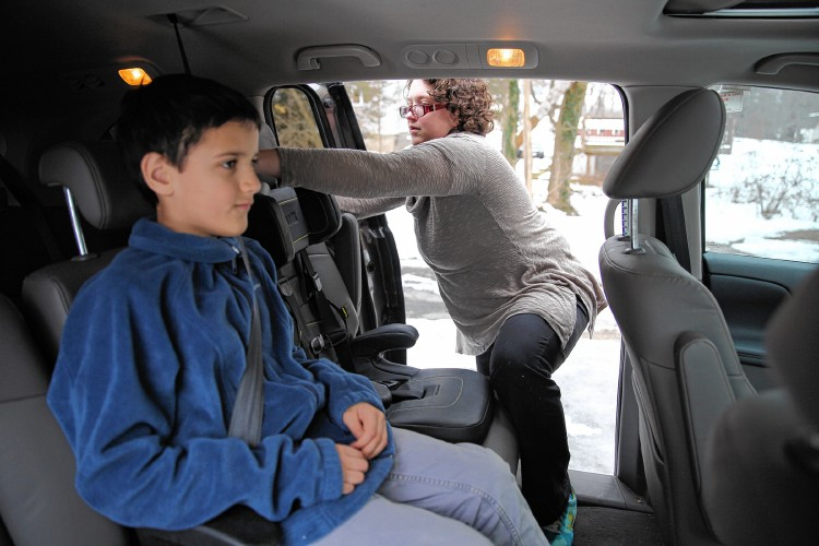 local safety technician cites studies showing lowered injury risk for kids under 13 kept in the back seat