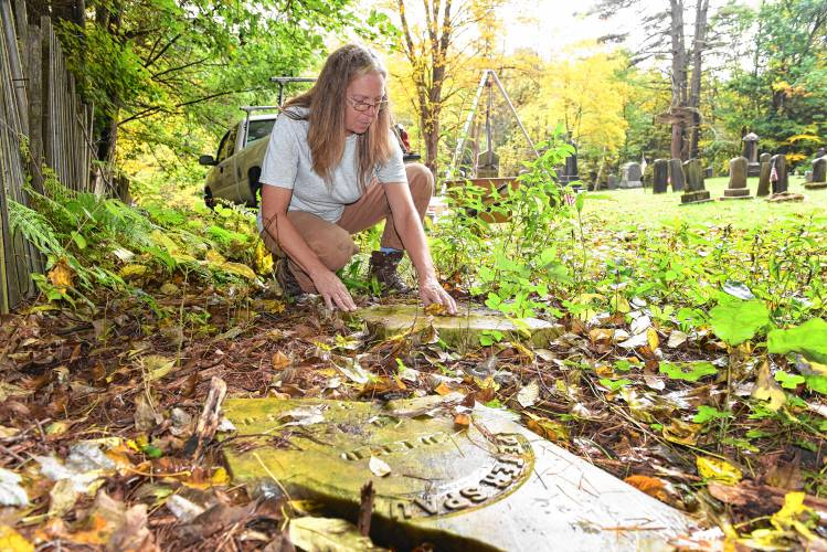 After finding Peter Spaulding's broken gravestone at the edge of Mount Hope Cemetery in Leverett, TaMara Conde, who operates Historic Gravestone Services, repaired it and put it back next to his wife's marker. Staff Photo/PAUL FRANZ