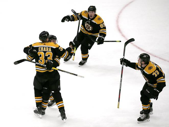 8ff55bf9377 Boston Bruins defenseman Zdeno Chara (33) hugs teammate Patrice Bergeron as  left wing Brad Marchand (63) and Charlie McAvoy (73) celebrate the winning  goal ...